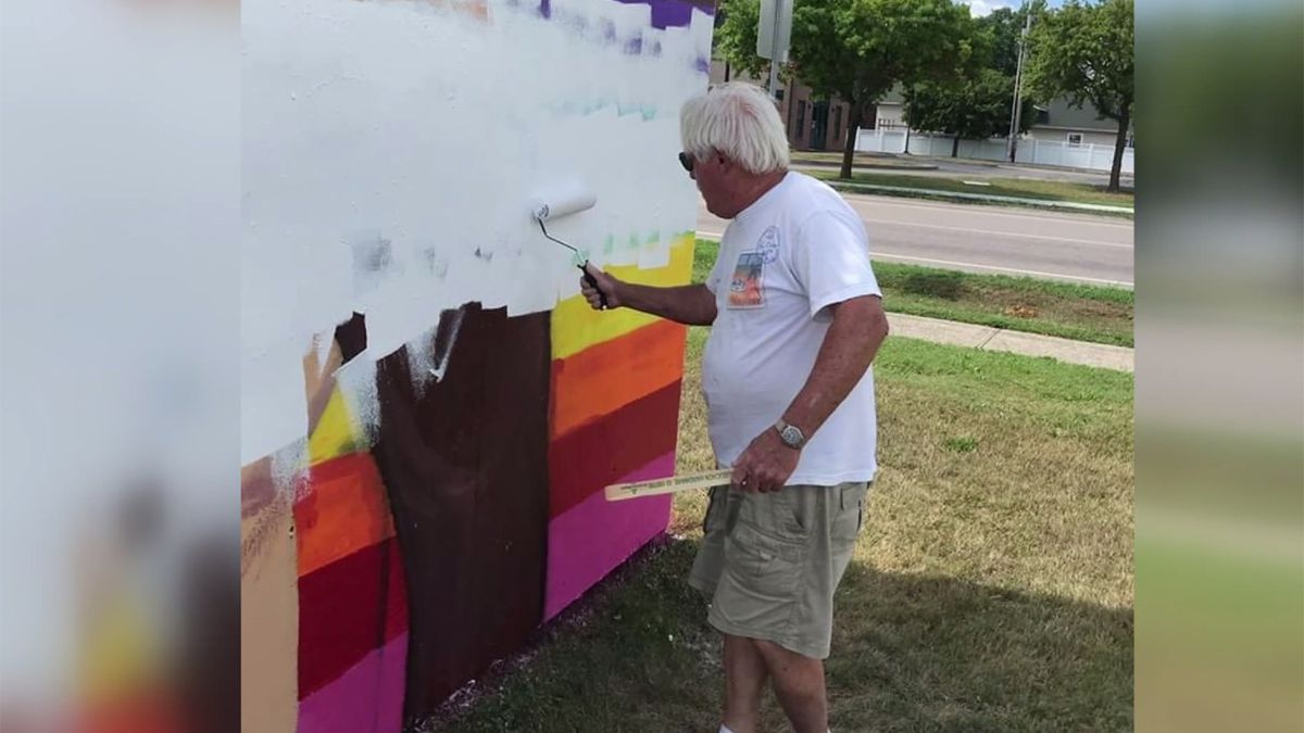 An unidentified man whitewashes a mural painted in Swanton as part of an art project.