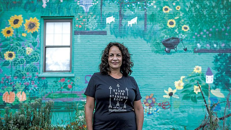 Gina Carrera standing in front of her mural on South Champlain Street.