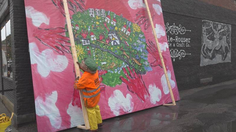Curatrix Alexis Smith prepares the 'Handout Number 27' mural for installation.