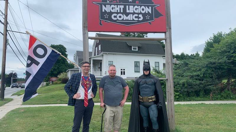 Night Legion Comics owner Jared Goodrich with caped crusaders outside his new Rutland store.