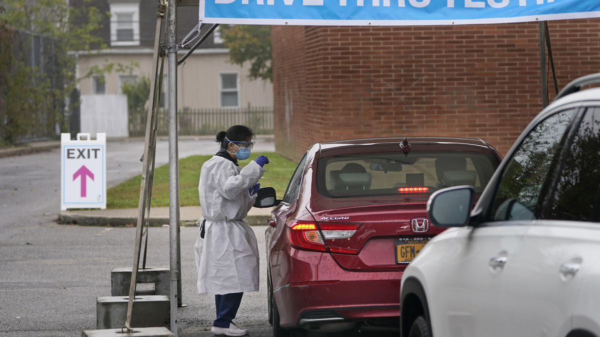 Medical personnel prepare to administer a COVID-19 swab at a drive-through testing site in...