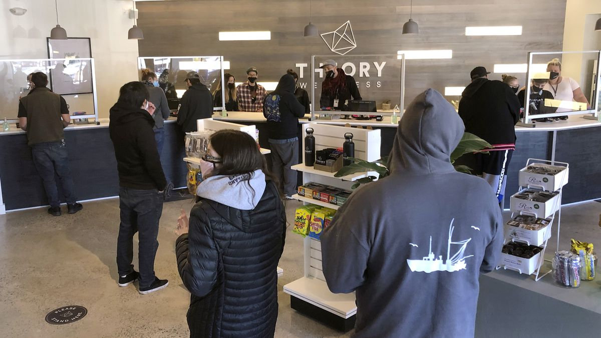 File - Buyers line up to purchase cannabis products at Theory Wellness in South Portland, Maine.