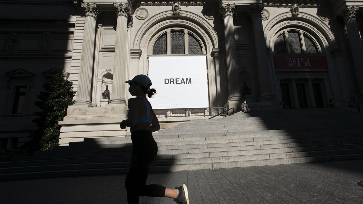 """A woman jogs past a banner by artist Yoko Ono at the Metropolitan Museum of Art, Thursday, Aug. 20, 2020, in New York. Ono's two banners on the front of the museum say """"Dream Together."""" The museum will reopen to the public Aug. 29, 2020. (AP Photo/Mark Lennihan)"""