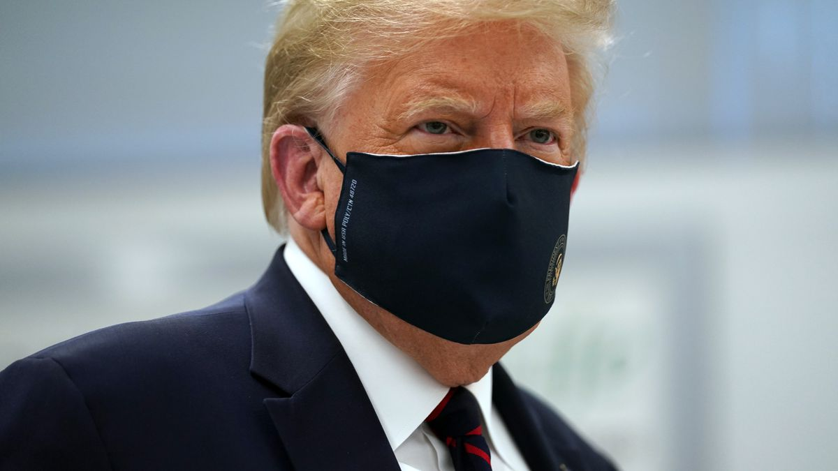 President Donald Trump wears a face mask as he participates in a tour of Bioprocess Innovation...