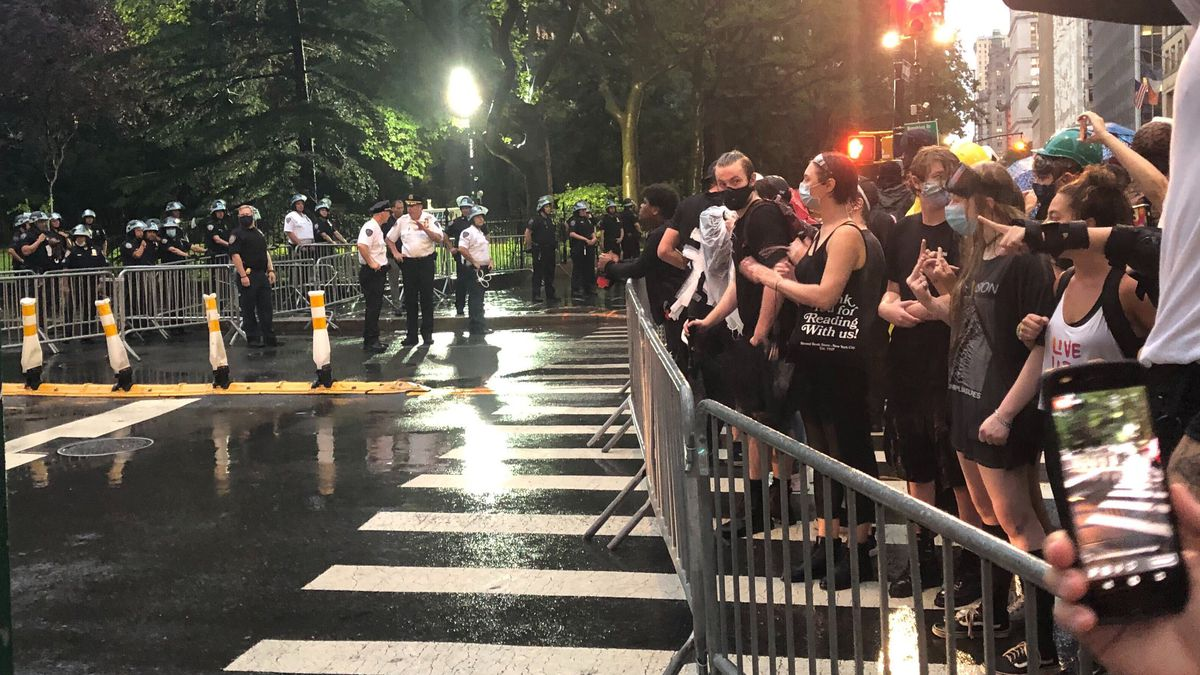 Protesters supporting Occupy City Hall stand behind barriers as members of the New York City Police Department are staged on the other side, Wednesday, July 22, 2020, in New York. Scores of protesters marched in the rain to re-sound their calls to stop funding the police department and ultimately abolish it. (AP Photo/Jennifer Peltz)