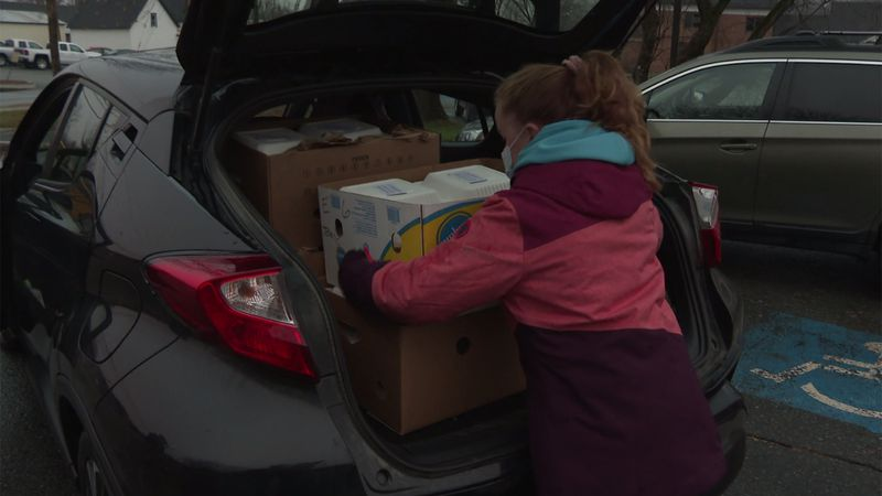 Boxes of Thanksgiving meals with all the fixings are packed into cars for people who need them.