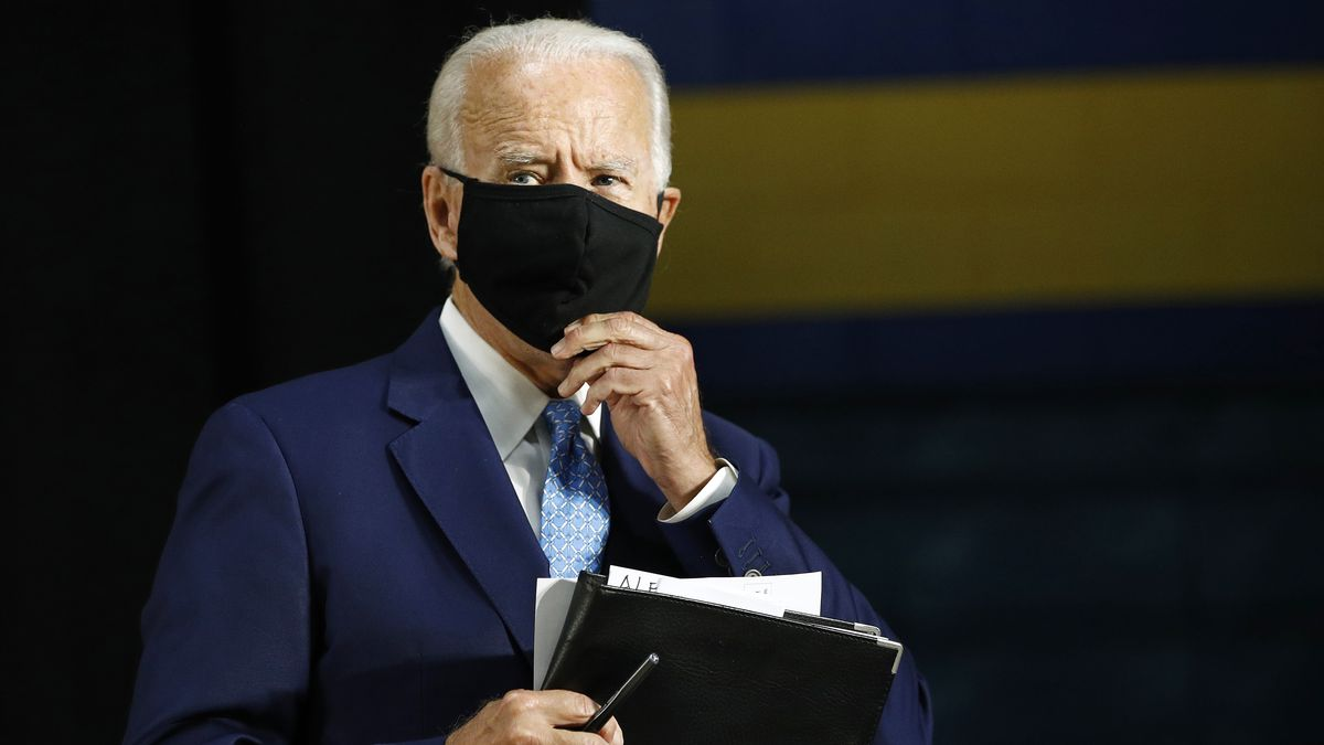 Former Vice President Joe Biden puts on a face mask to protect against the spread of the new...