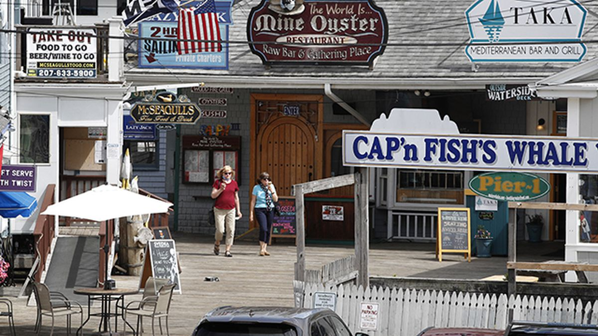 Tourists walk by newly reopened restaurants, Tuesday, June 9, 2020, in Boothbay Harbor, Maine. Many Maine tourists towns have seen a sharp drop in the number of visitors due to the coronavirus pandemic. (AP Photo/Robert F. Bukaty)