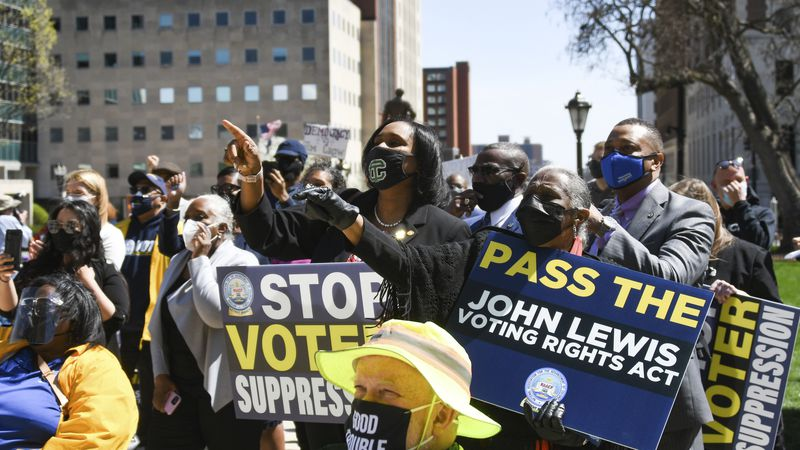 People rally outside of the Capitol in Lansing, Mich., Tuesday, April 13, 2021, during a rally...