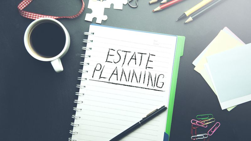 estate planning text on notepad  with stationary on table