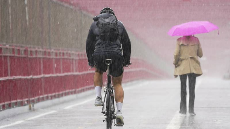 A pedestrian and cyclist make their way over the Williamsburg bridge in a heavy downpour of...