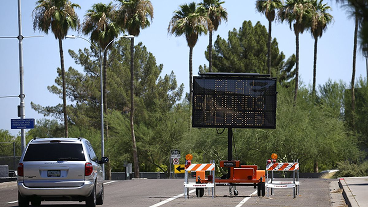 A vehicle drives past a temporary sign set up at an entrance at Kiwanis Park lets patrons know what is closed as new rules have shut down many activities due to the surge in coronavirus cases Tuesday, June 30, 2020, in Tempe, Ariz. (AP Photo/Ross D. Franklin)