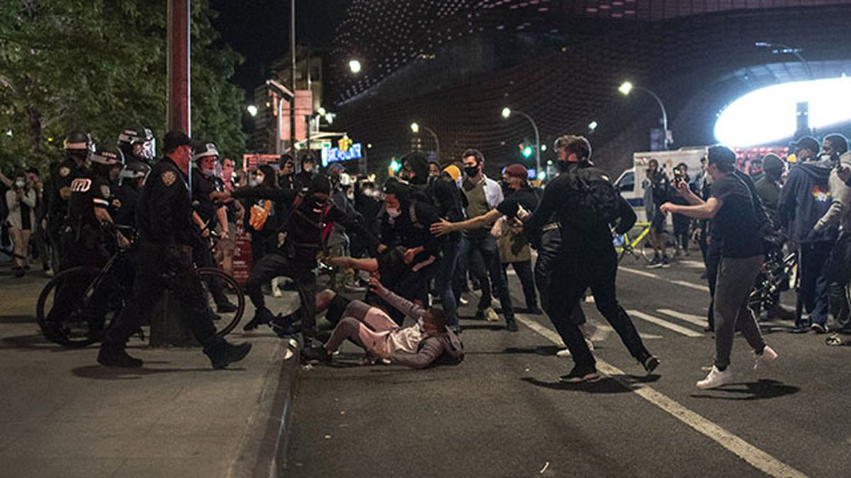 Police move to detain protesters as they march down a street during a solidarity rally for...