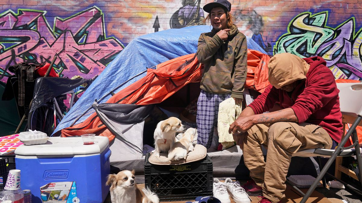 Lucio Lopez, left, talks with friends as he stands in a tent that is part of a homeless...