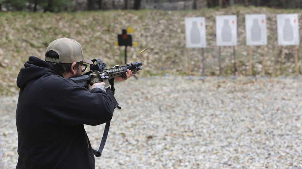 A shooter fires a rifle at a target at Slate Ridge Vermont, an unpermitted gun range and...