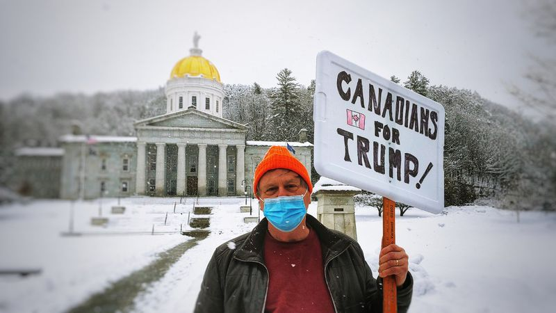 One man holds a Canadians for Trump sign outside the Statehouse building in Montpelier.