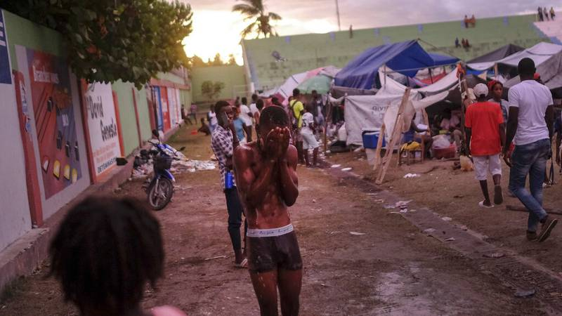 A youth bathes at a makeshift camp for people whose homes collapsed during the earthquake, at a...