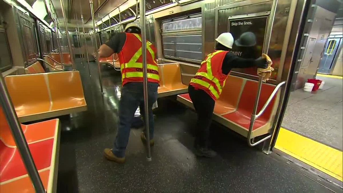 Workers disinfect a New York subway as the city prepares to begin the reopening process....